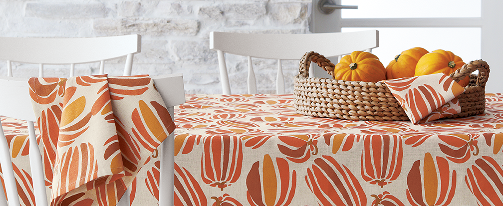 Linen tablecloth with pumpkin pattern under a rattan centerpiece bowl of mini pumpkins on a white ktichen table