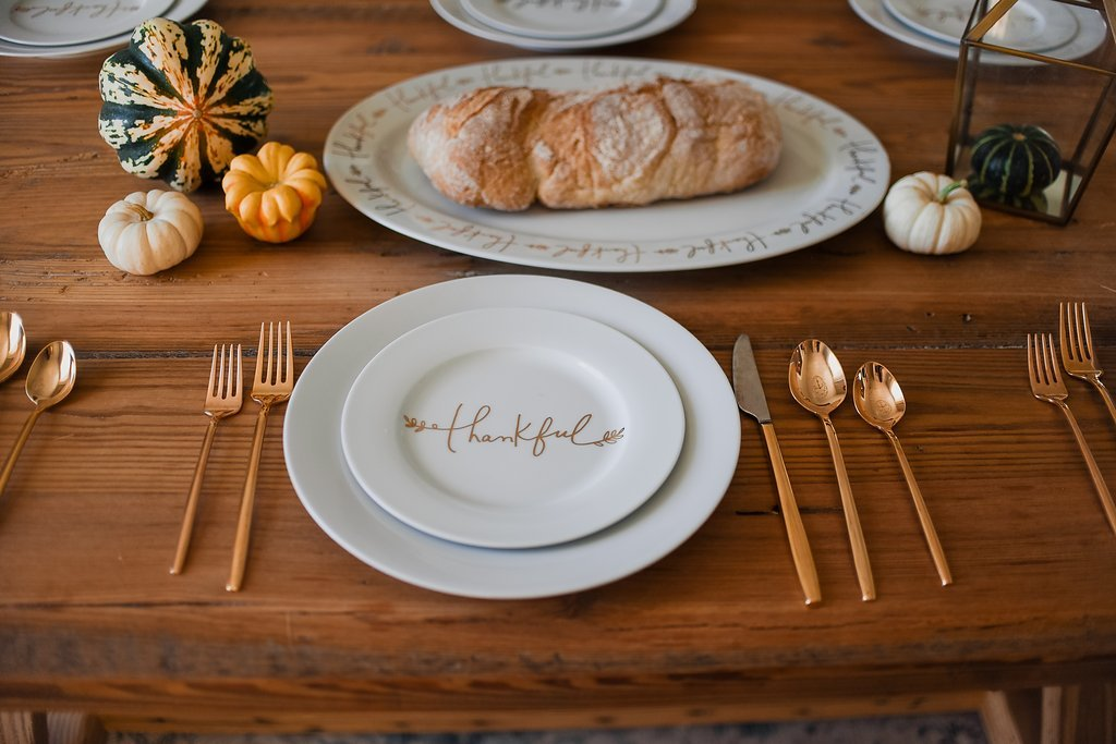 Thanksgiving place setting with white thankful dinner plates and rose gold flatware on a wood dining table