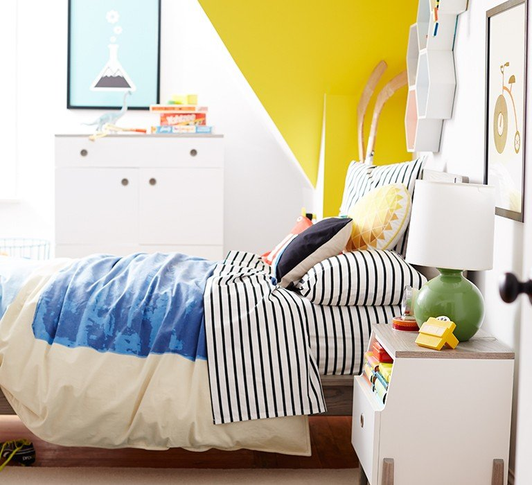 A small kids bedroom is decorated with bright colors and a yellow wall.
