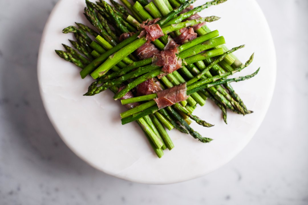 Prosciutto wrapped asparagus on a white plate