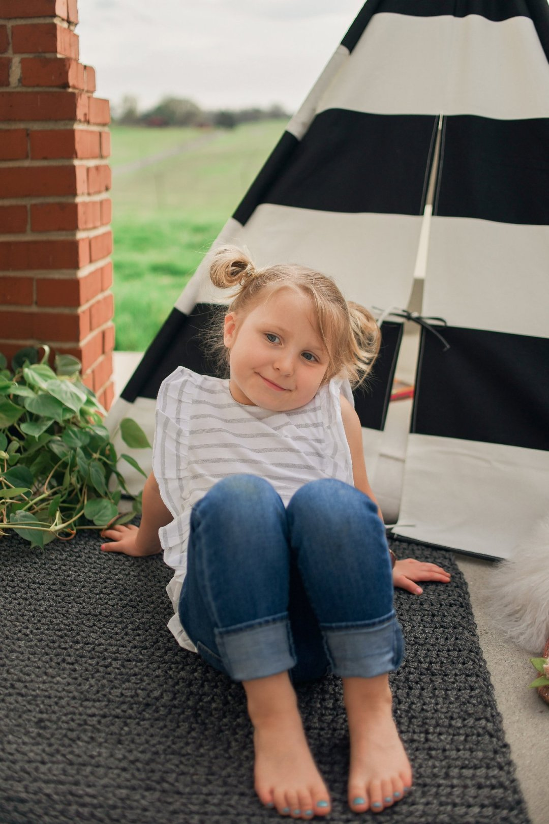 Little girl sitting on rug with teepee in background