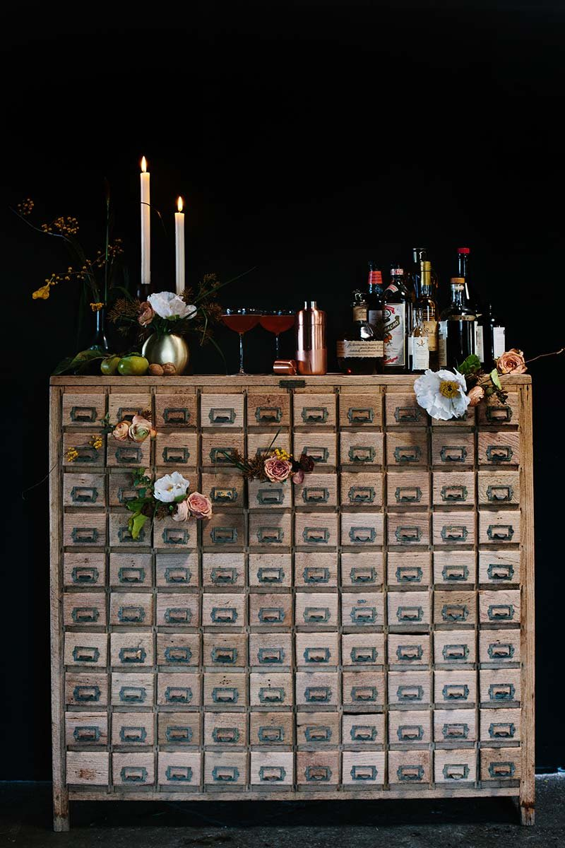 Rustic wood sideboard decorated with flowers and used as a makeshift home bar
