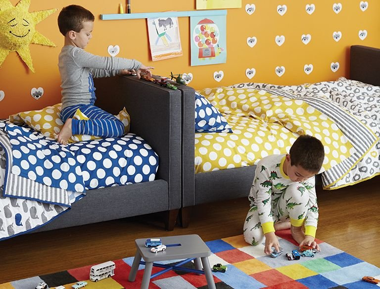 Two young boys play in their shared bedroom.