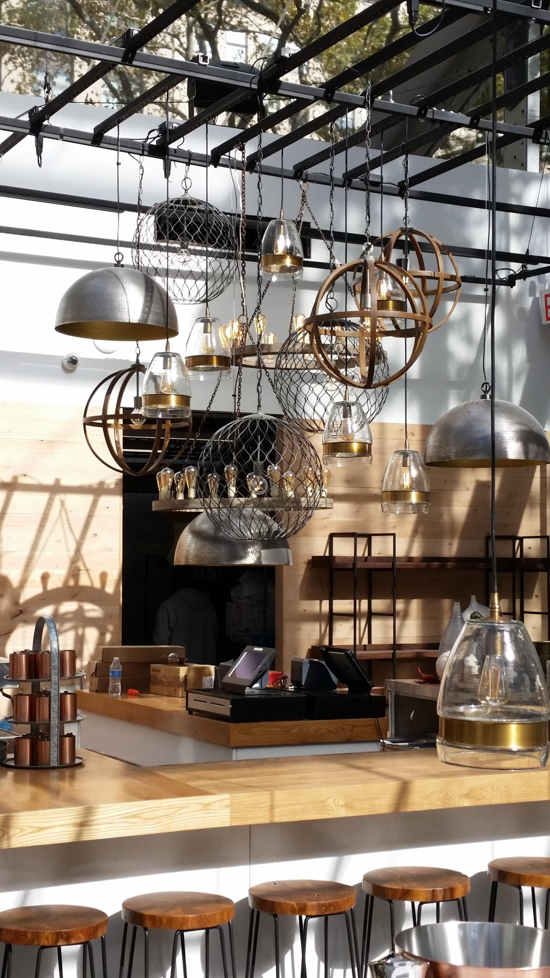 Wooden bar and wood and metal bar stools under a cluster of pendant lights at Public Fare Bryant Park