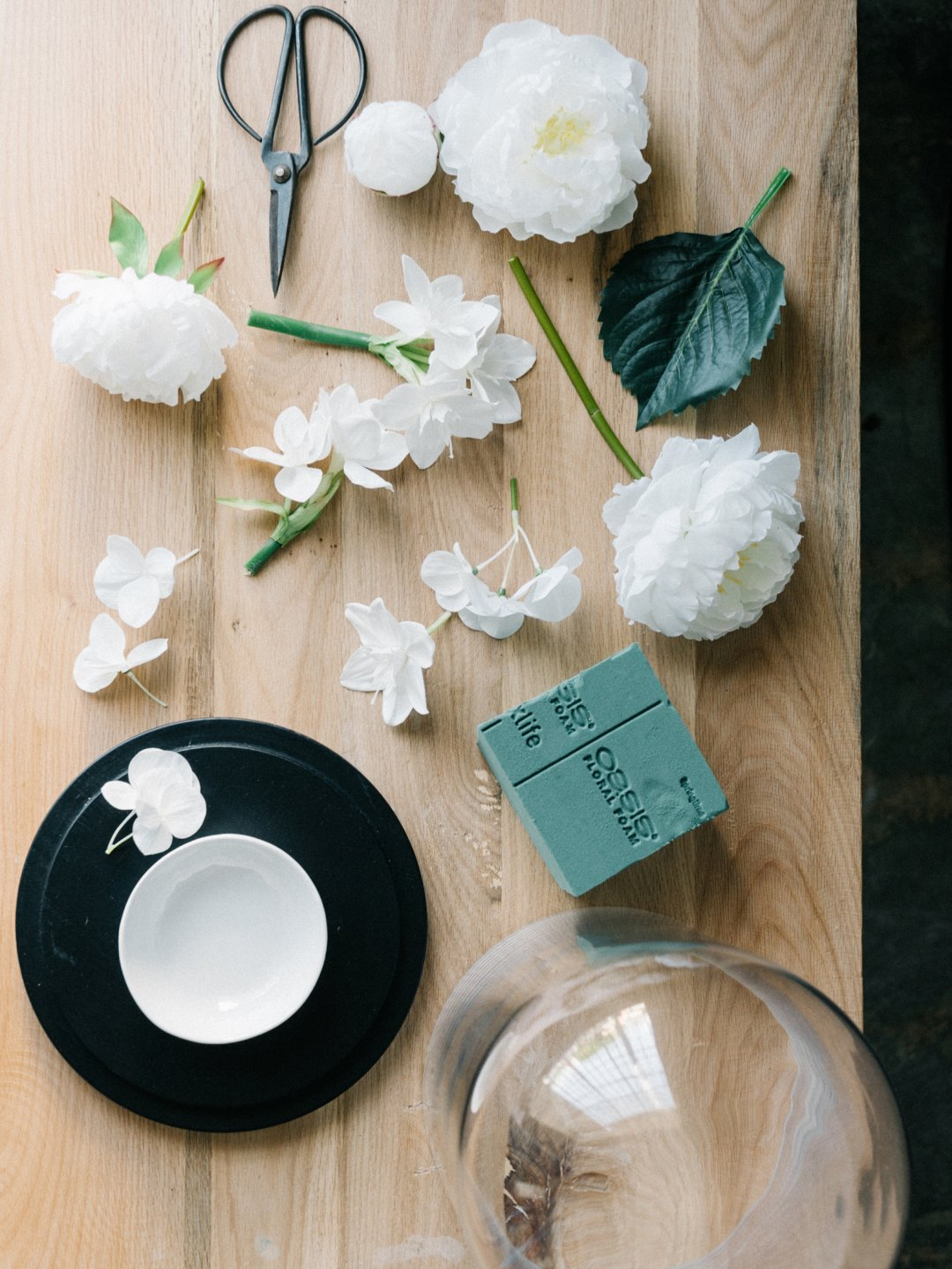 white flowers, scissors, and floral foam sit on a wood table ready to be displayed in a glass container
