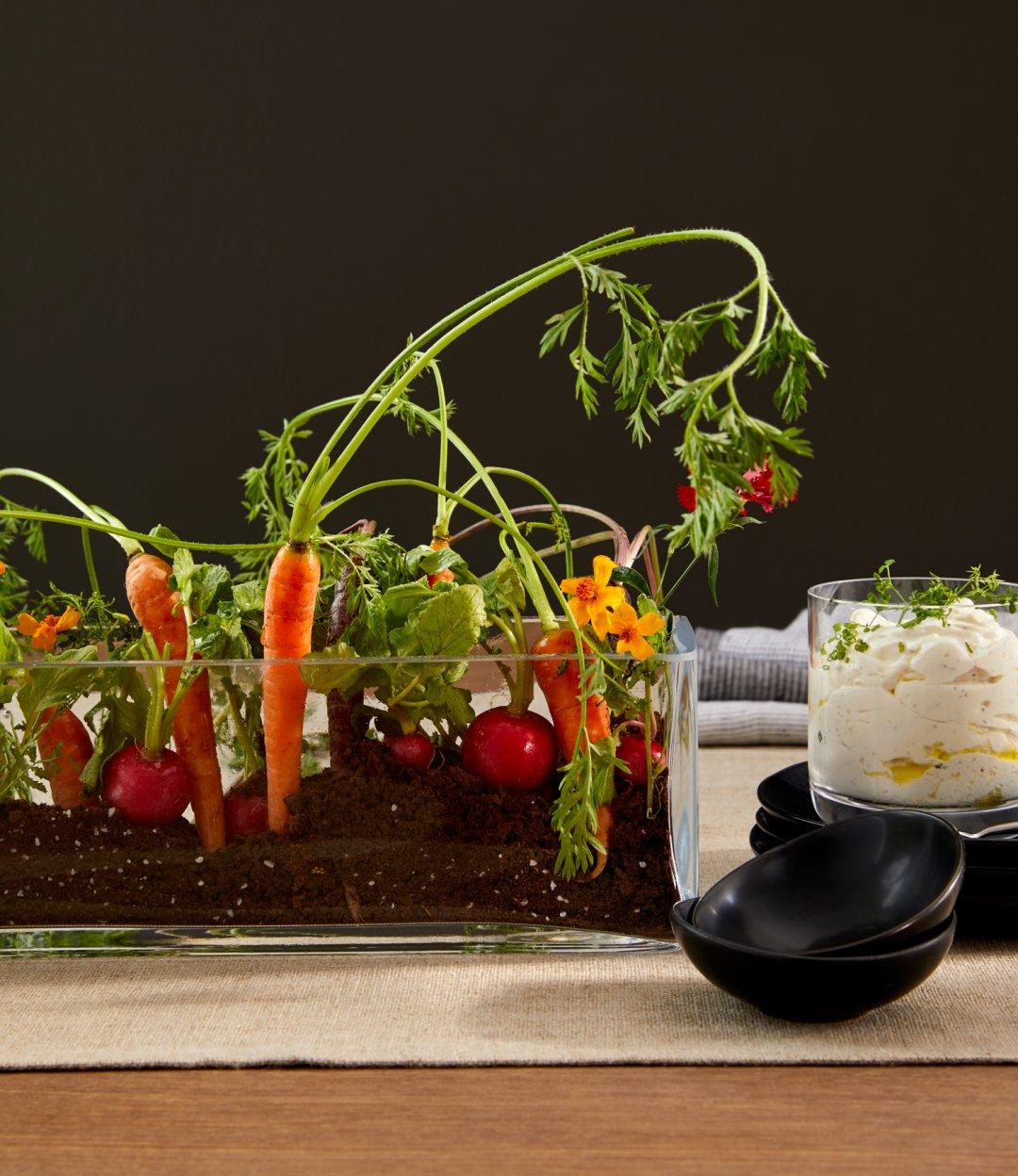 Veggies displayed in edible dirt dip in long glass vase