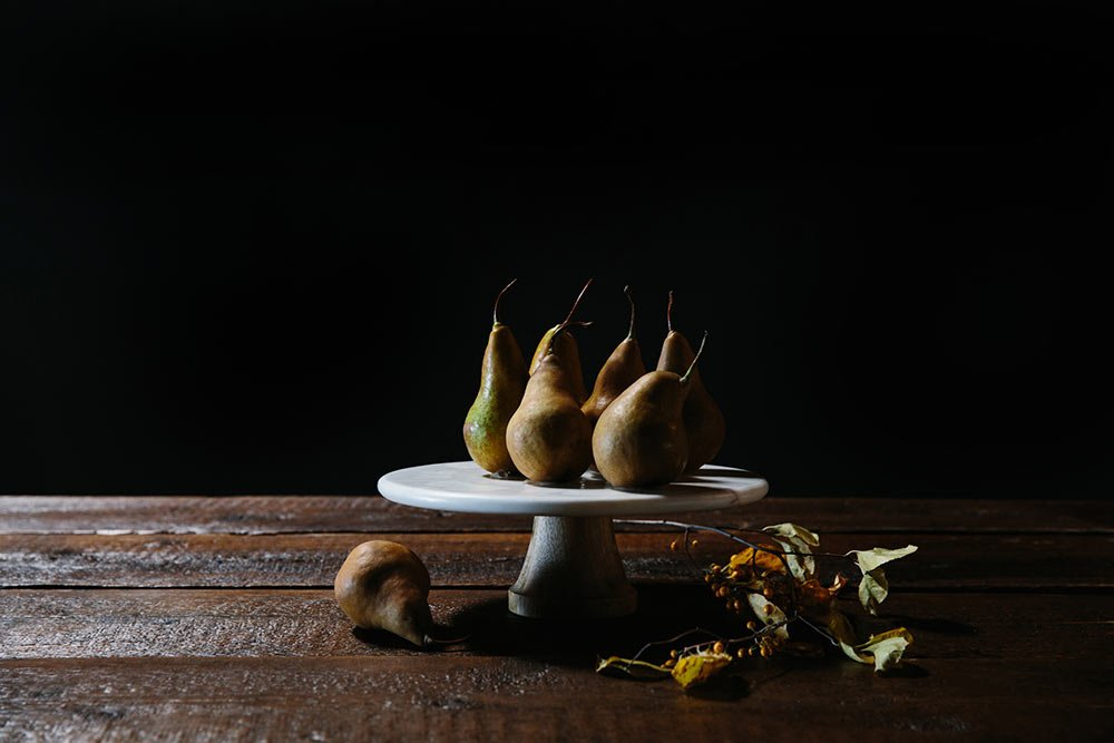 Brown and green pears displayed on a white cake server on a wood table