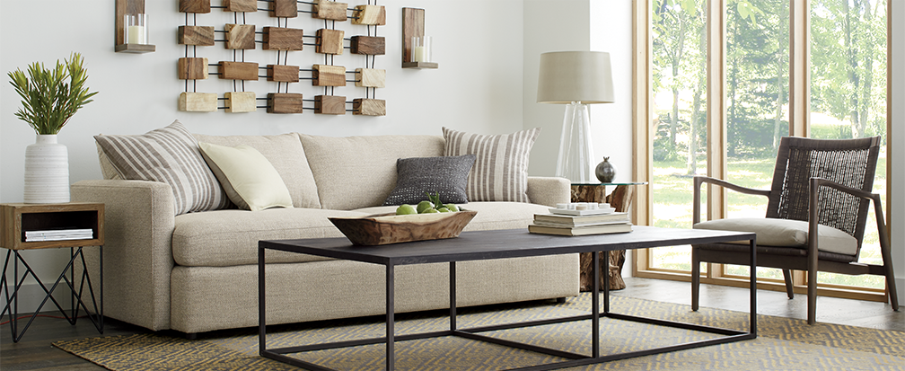 Lounge II tan sofa in a contemporary living room with mid-century modern side table and coffee table