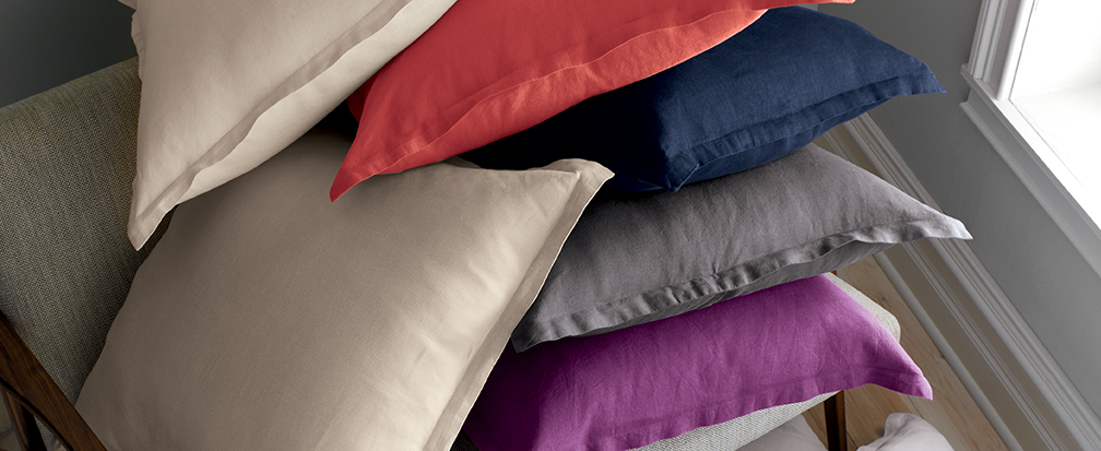 A stack of pillows in a variety of colored pillow shams and pillowscases on a chair