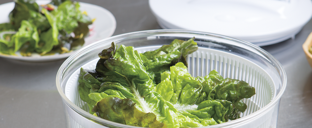 Dark leafy greens in a white plastic salad spinner with a plate of salad in the background