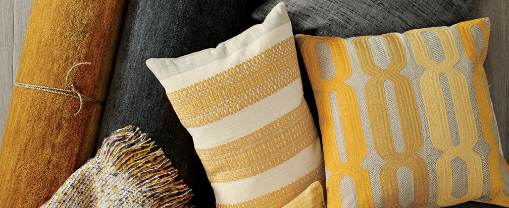 Burnt orange and yellow throw pillows with matching throws and rugs