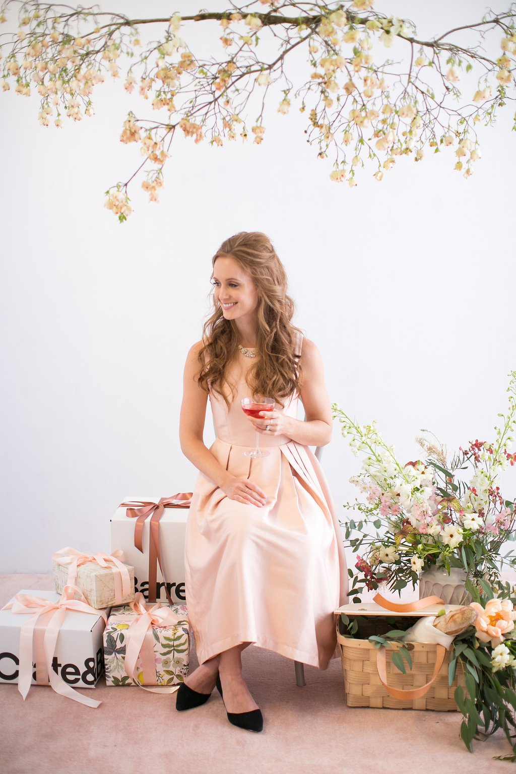 Bride sitting by Crate and Barrel boxes with pink cocktail at bridal shower