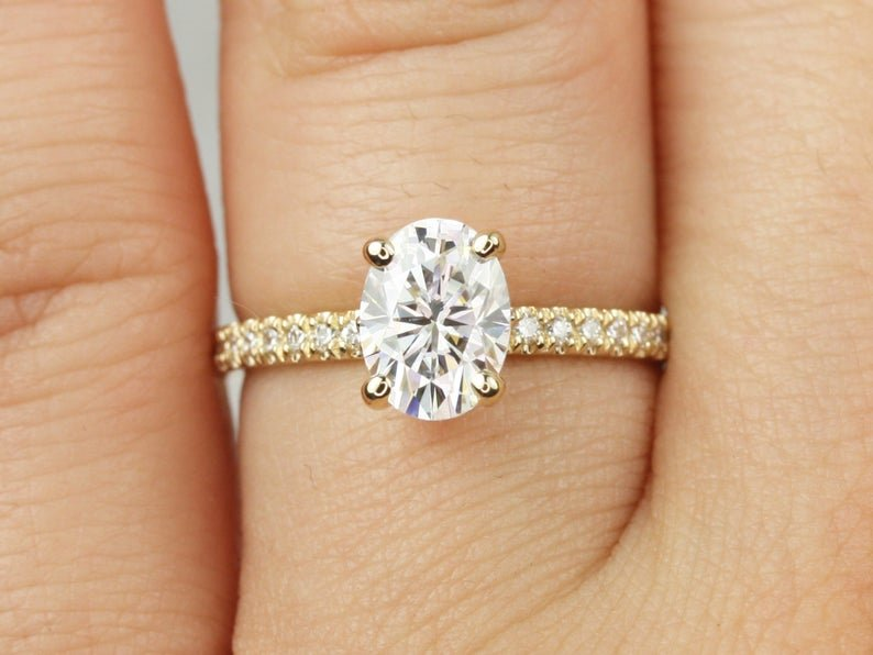 solid gold oval engagement ring on finger