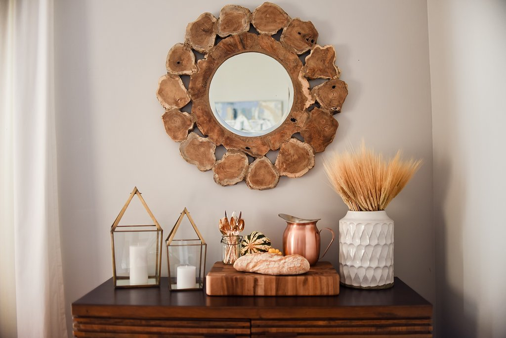 A natural wood mirror hanging on the wall above a sideboard decorated with autumnal accents