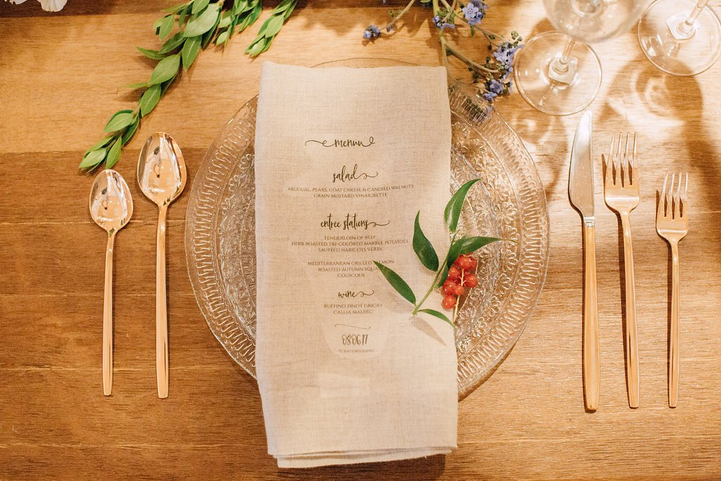 Place setting with glass plates, rose gold flatware, and menu on napkin
