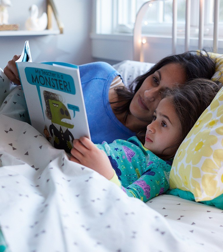 A mom and daughter snuggle together to read a bedtime story.
