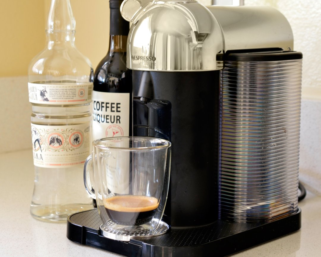 a partially filled mug of espresso on an espresso machine near a bottle of vodka and coffee liqueur