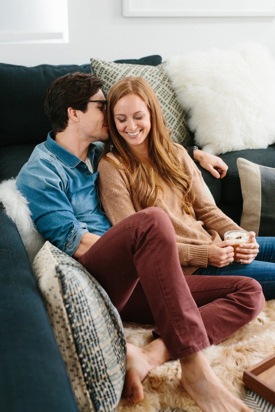 Couple cuddling on sofa with several large throw pillows