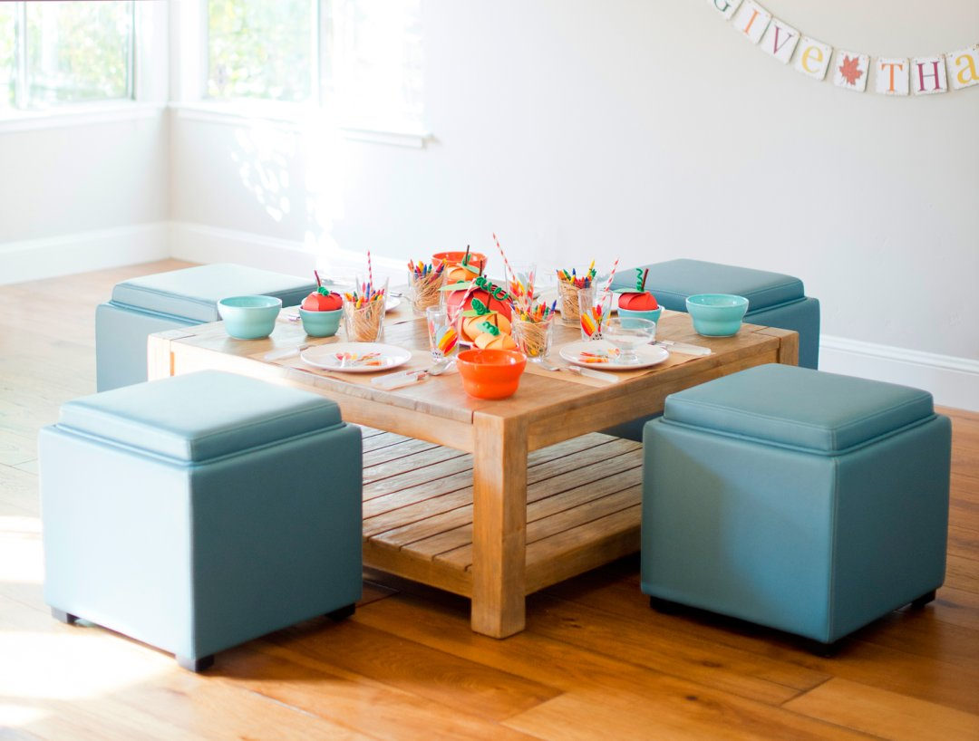 Small wood table decorated for Thanksgiving surrounded by four blue ottomans  to use as seats