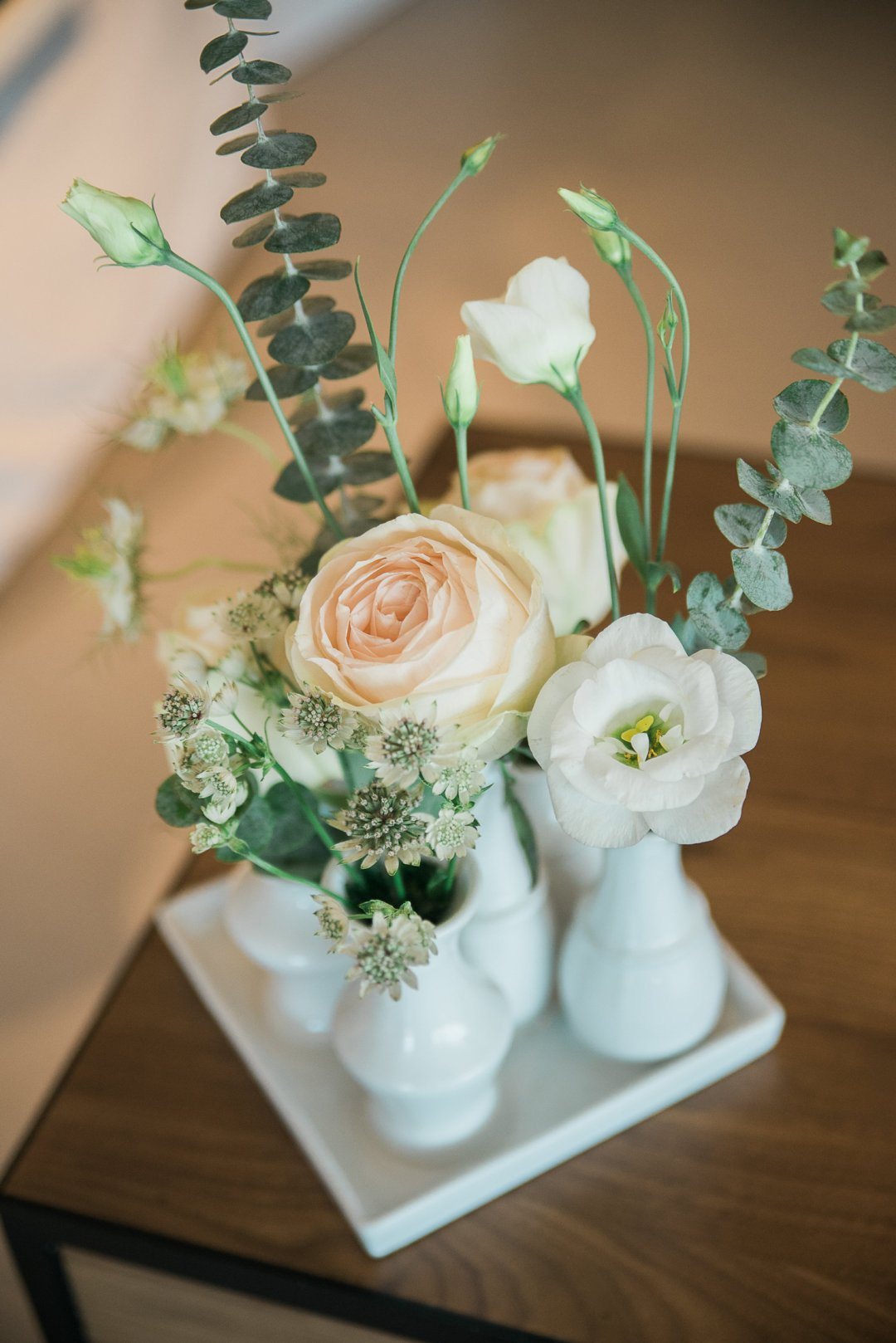 Collection of white flowers in small white vases