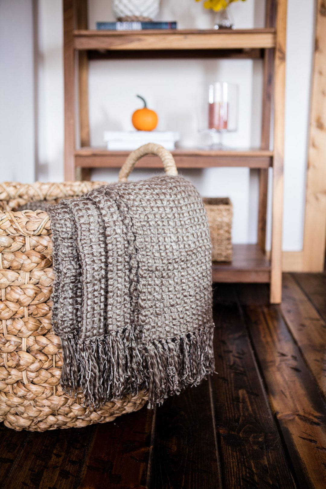 Brown throw draped over the edge of a rattan basket