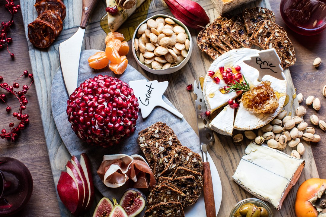 Wooden cheese board covered with pomegranate-encrusted goat cheese, honey-drizzled brie, mixed nuts and thinly-sliced prosciutto
