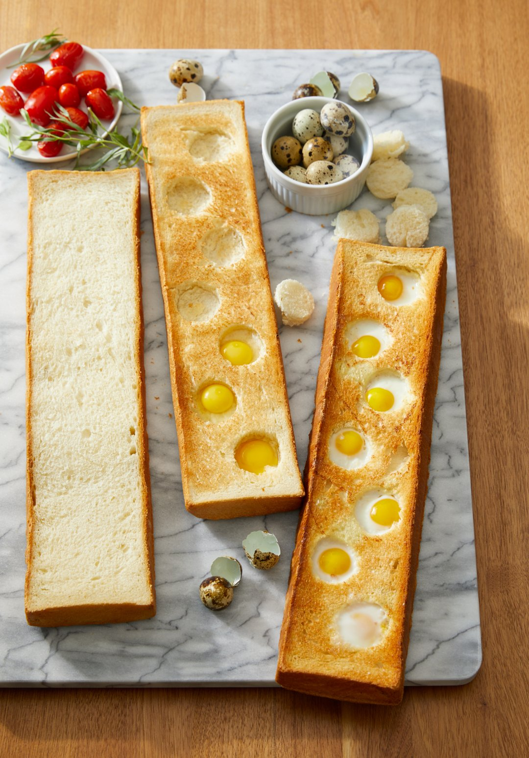 Three halved bread loaves punctured with shallow holes filled with quail eggs laid out on a marble board
