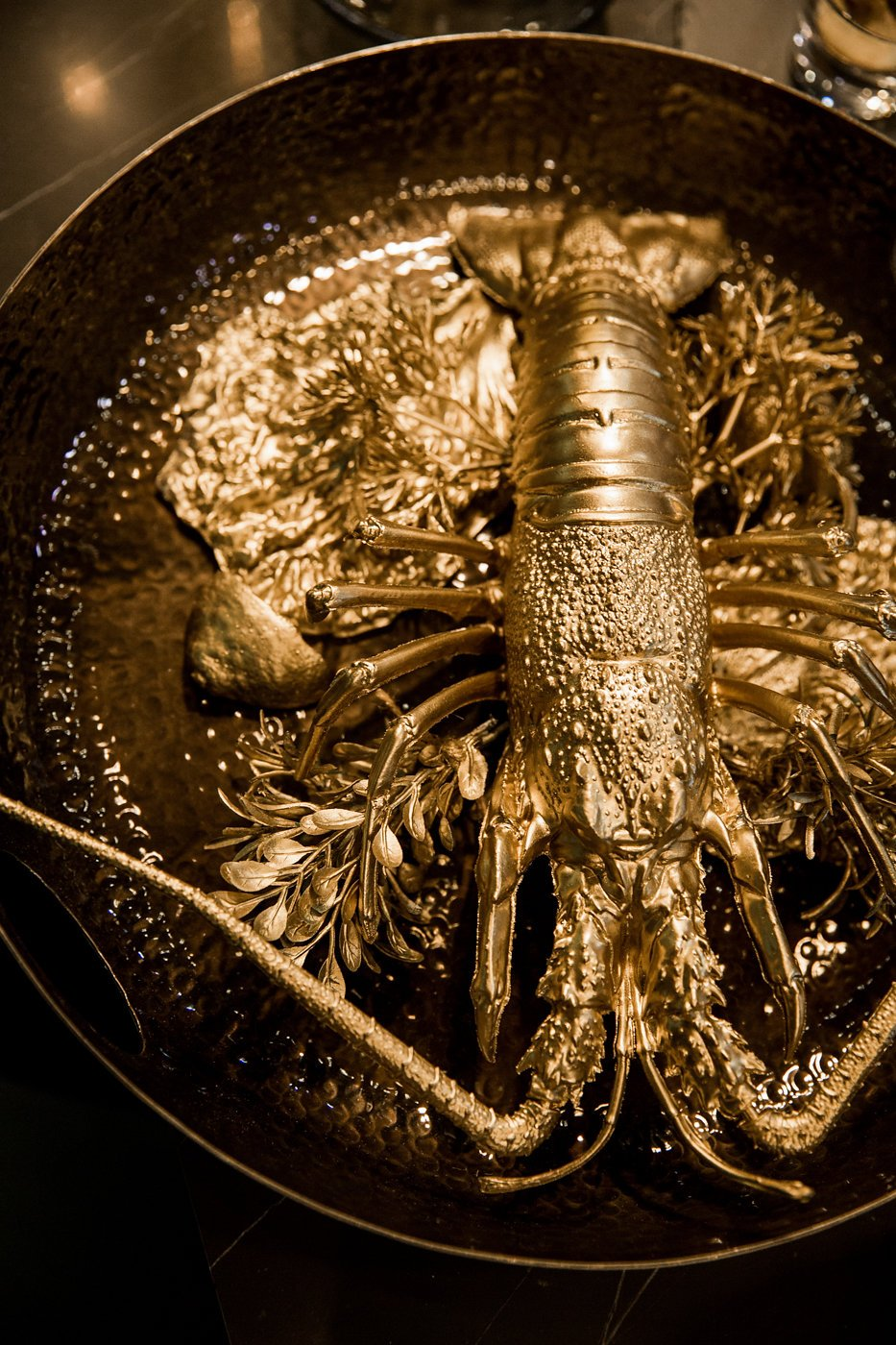 Golden painted lobster in a black cooking pan