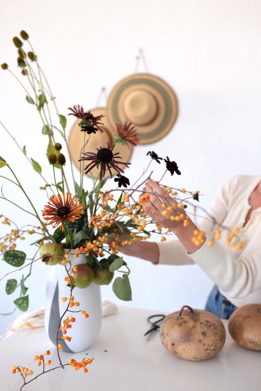 Arranging black eyed susans in a fall bouquet in a white vase