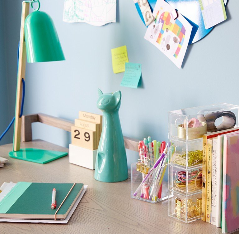 A girls desk is very organized with containers for pens and pencils.