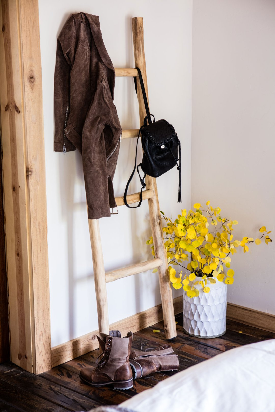 A suede jacket and small backpack hanging ona decorative wooden ladder next to a vase of yellow flowers on the floor