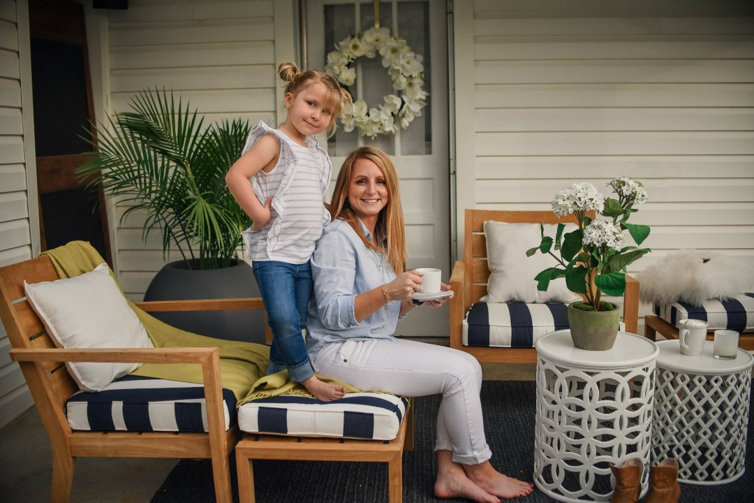 Daughter standing on chair beside sitting mother, both smiling