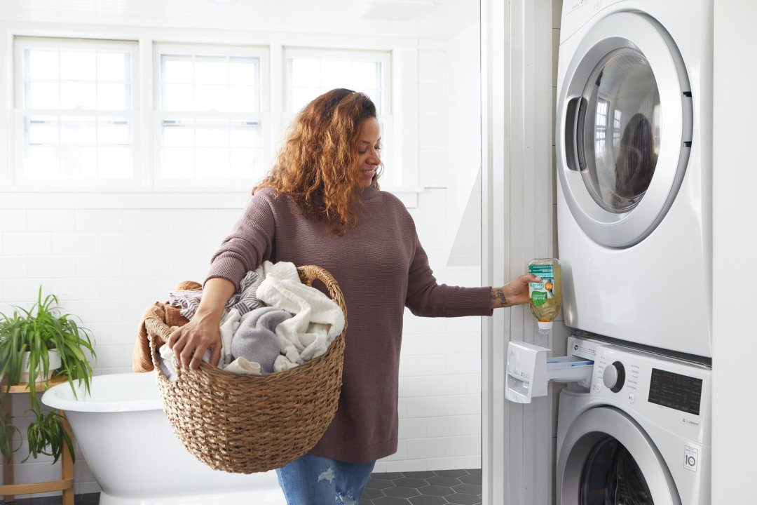 person holding laundry basket while dosing laundry detergent into HE washer