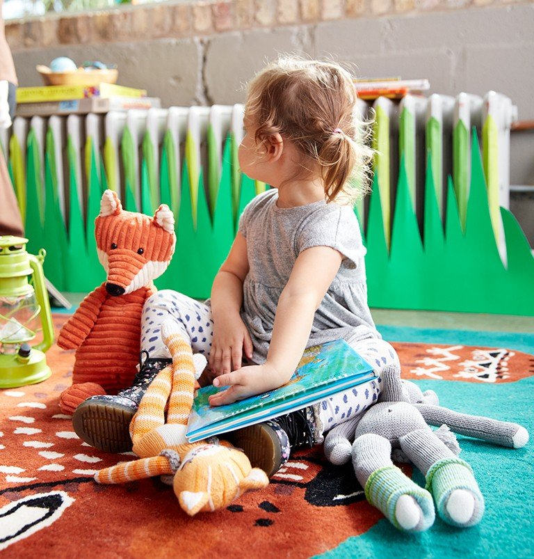 A soft rug on the floor creates a place for a young girl to play with her stuffed animals