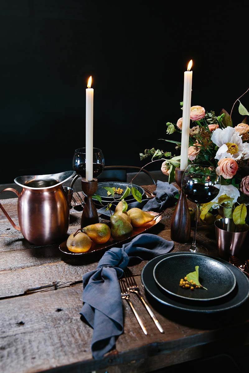 Pears in long copper centerpiece bowl next to a copper water pitcher and taper candles in wood candle holders in center of dining table