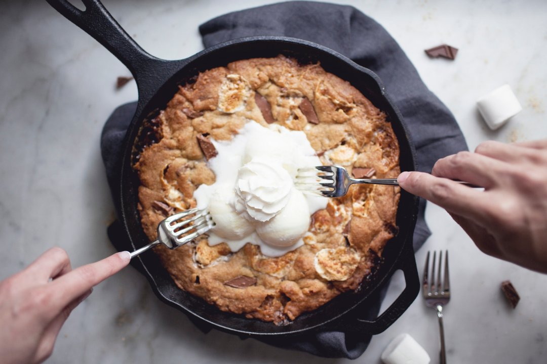 Two hands with forks digging into cookie skillet