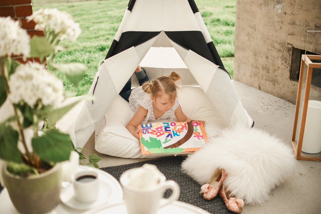Little girl reading book in teepee