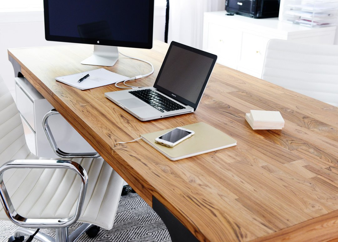 Wood home office desk with a laptop, desktop screen, notebook and cell phone on it