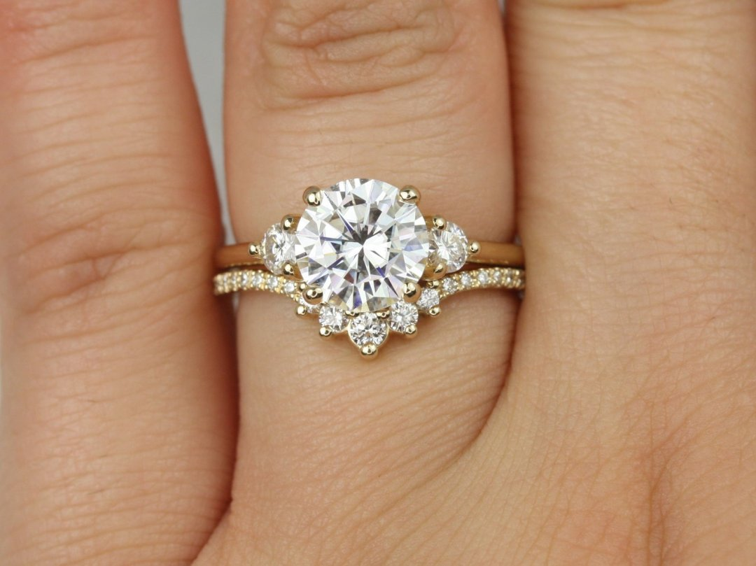 solid gold engagement ring with band shown on hand