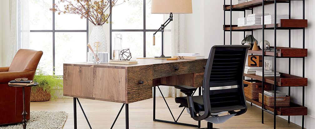Modern office furniture, including a wooden desk, bookshelves and leather chair
