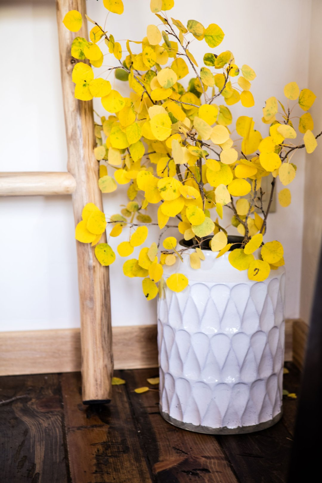 Large white ceramic vase of yellow leaves