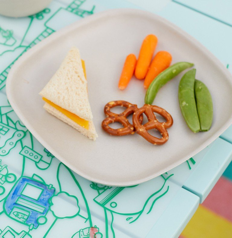 A plate with small snacks like pretzels and peas