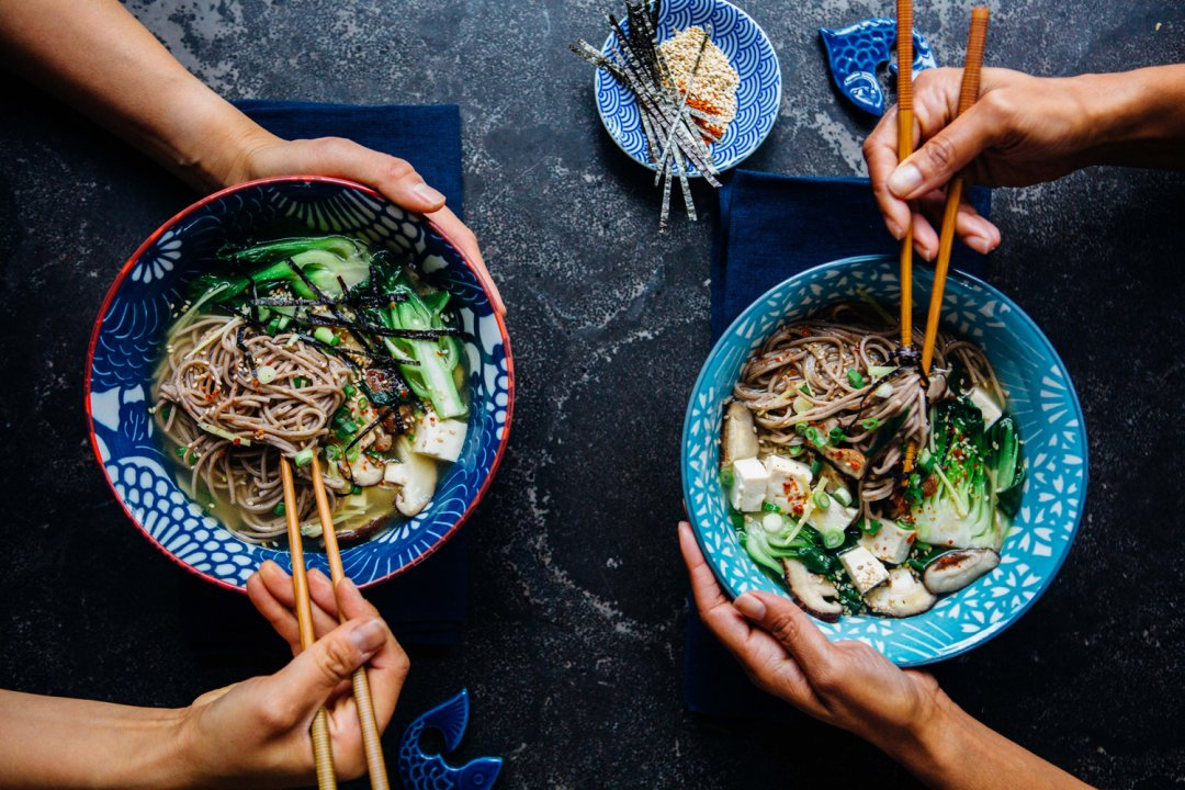 Two people eat vegan miso soba noodle soup with chopsticks