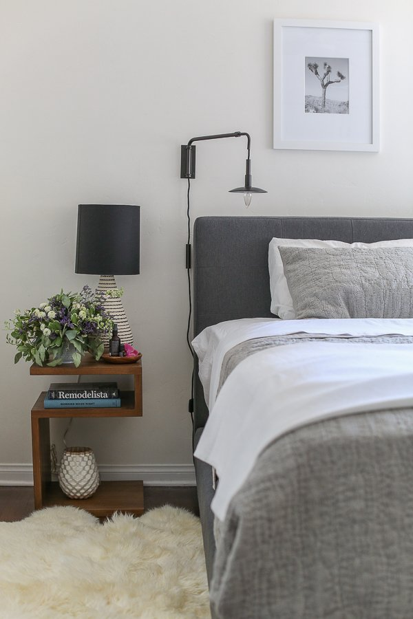 Bed with grey bedspread, shag rug, bedside table with lamp and flowers, and reading overhead lamp
