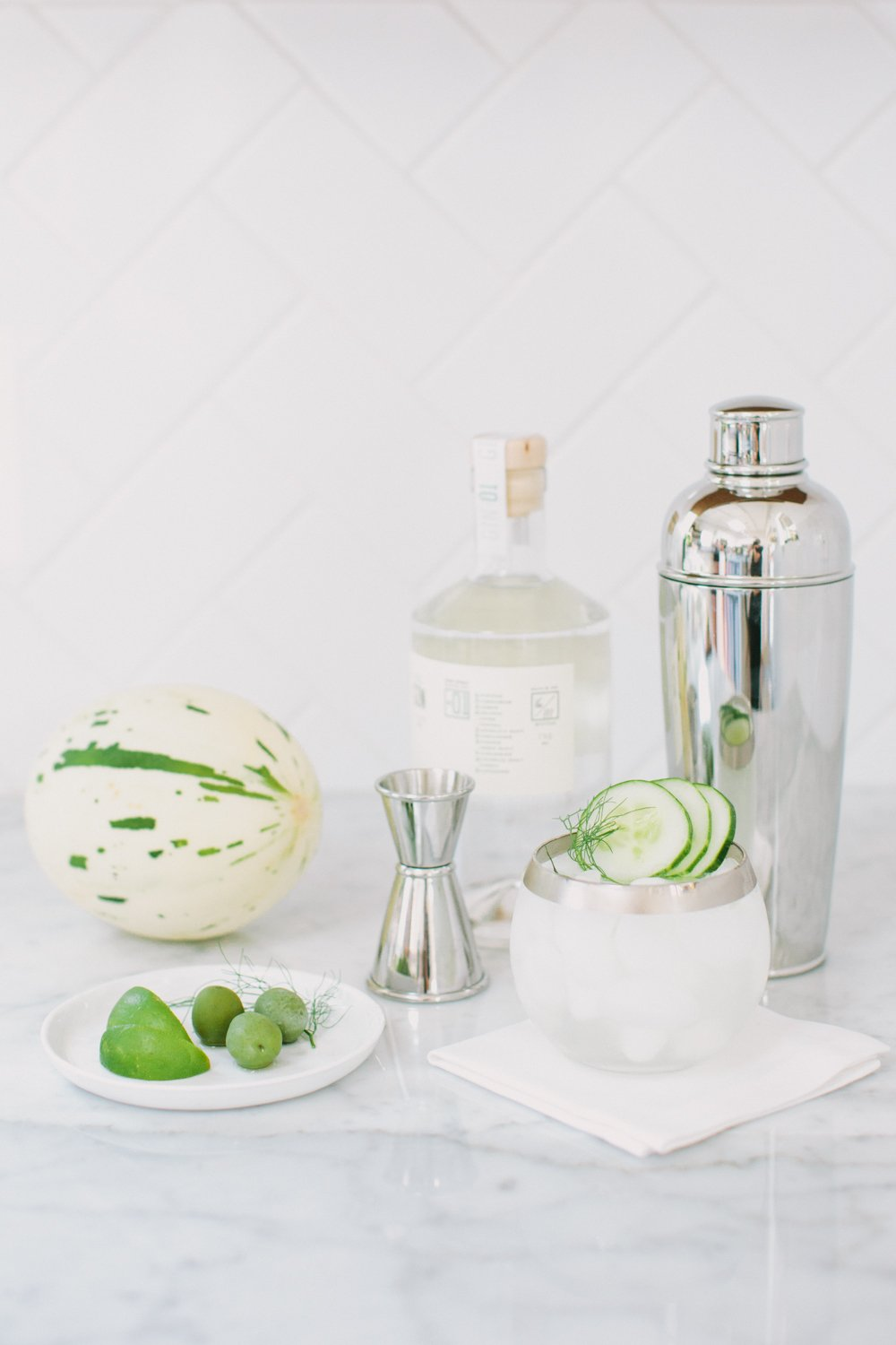 Cocktail ingredients and tools on a marble surface next to a plate of garnishes including lime, dill and mint