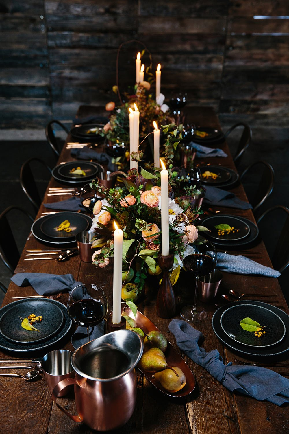 Black place settings on a dark wood table decorated with white and pink florals and rustic green botanicals