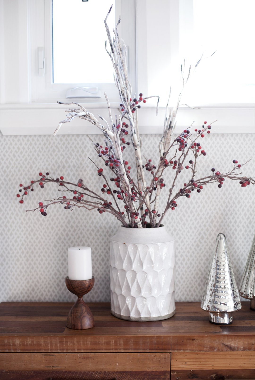 Cranberry and birch branches in a large white vase on a wood sideboard