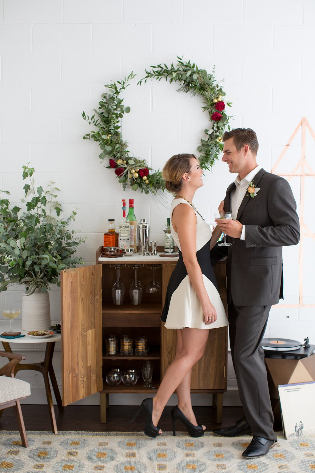 man and woman dressup up enjoying a martini in front of a bar cart