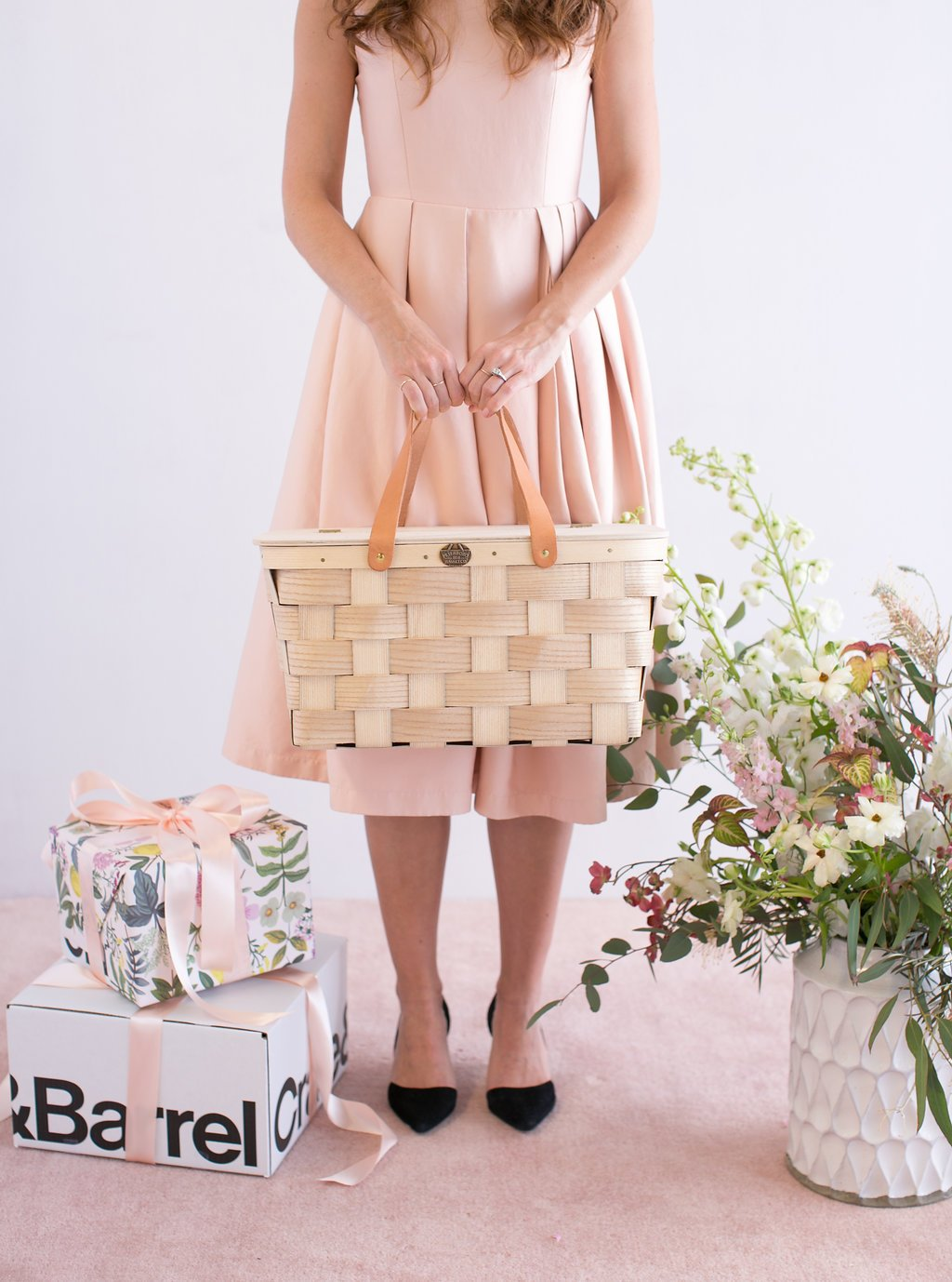 Bride holding picnic basket standing next to Crate and Barrel boxes at spring wedding shower
