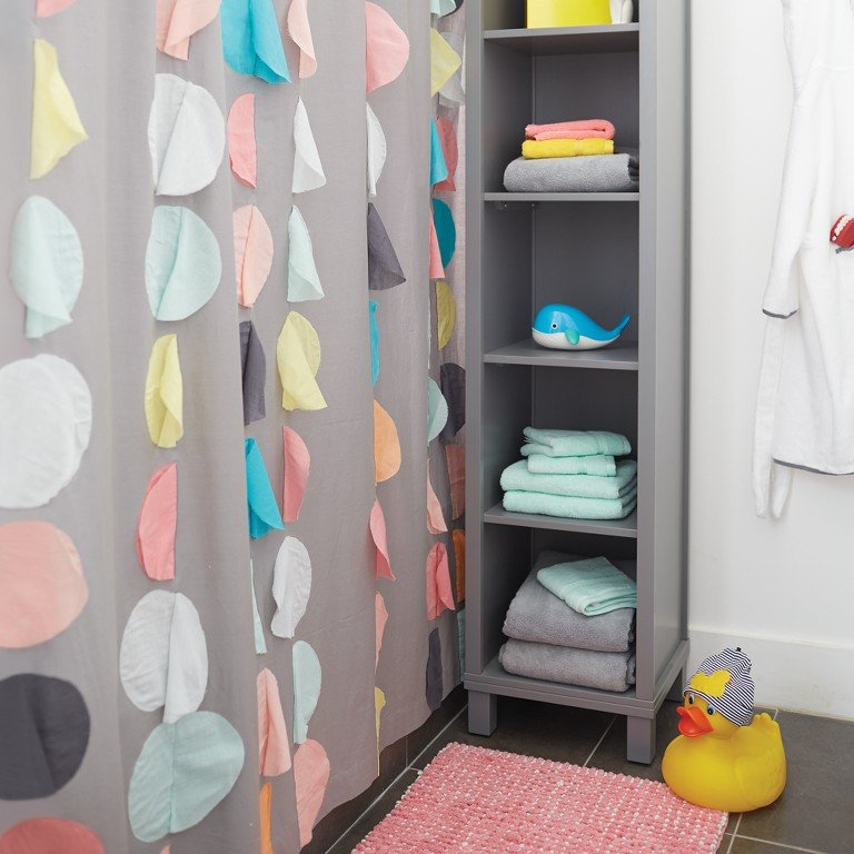 Next to a shower, a shelving unit adds extra places to put towels and bath accessories